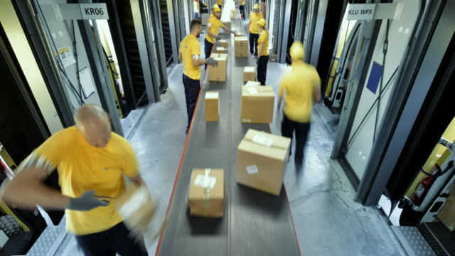 time-lapse workers taking packages off the conveyor belt for further distribution - officina video stock e b–roll