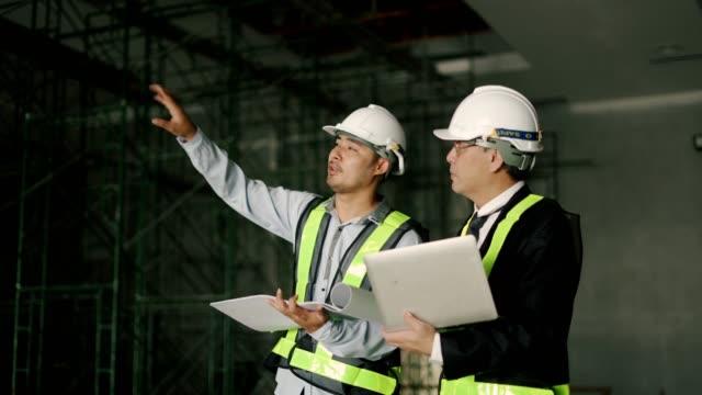 工場で話したり笑ったりする労働者 - 設計図点の映像素材/bロール