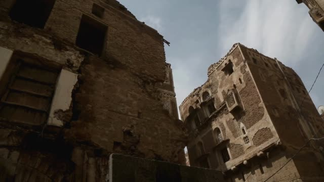 workers throw debris and bricks from the top of the buildings of the historic old quarter of sana'a still standing as recent rains have threatened... - unesco world heritage site点の映像素材/bロール