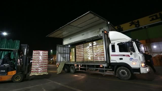 Workers transport boxes of vegetables at Garak Market operated by Seoul AgroFisheries Food Corp in Seoul South Korea on Wednesday Jan 15 Trucks...