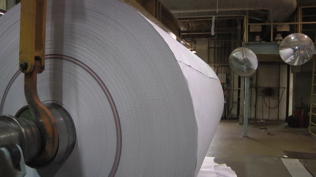cu pan workers trim new roll of paper and moves with mechanical hoist at paper mill / manistique, michigan, usa - paper mill stock videos and b-roll footage