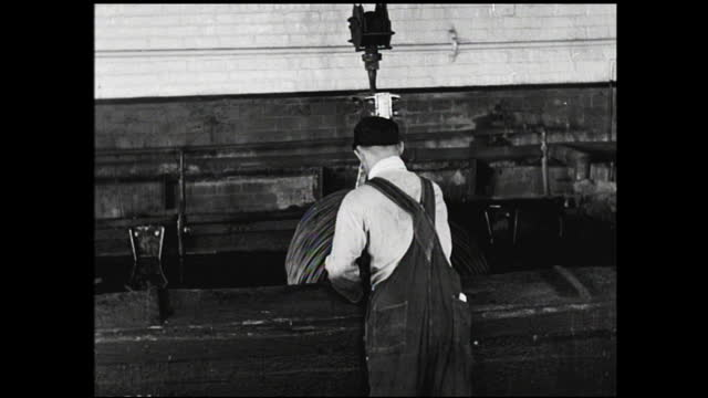 """workers tying together coils of wire on the conveyor belt; worker loading wire onto overhead crane and wire is dipped into acid bath, label """"position... - 1940 1949 video stock e b–roll"""