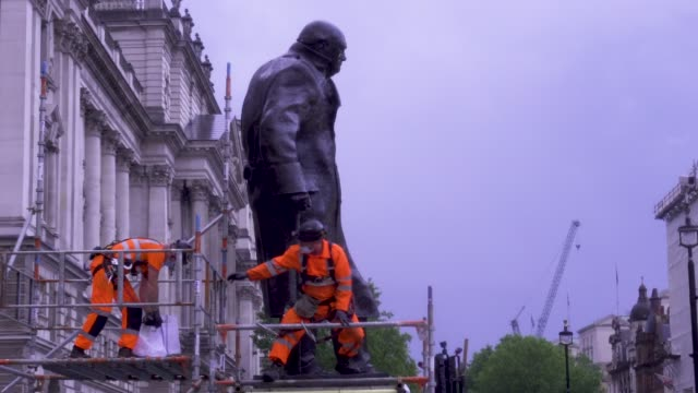 workers uncover the statue of winston churchill in parliament square on june 17, 2020 in london, england. the statue was covered up to protect it... - video stock videos & royalty-free footage