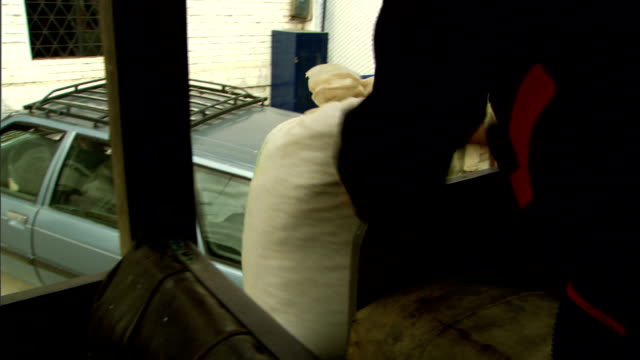 workers unload a bag of coffee beans from a vehicle. - 麻袋点の映像素材/bロール