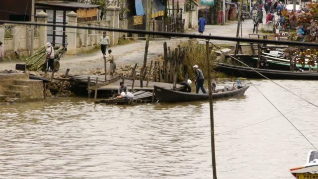 workers unload boat in inle lake, myanmar - spoonfilm stock-videos und b-roll-filmmaterial