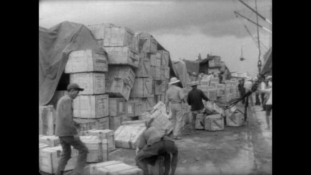 workers unload cargo boxes at port in saigon / cu of open boxes on ground containing american goods including clocks and sunglasses / people sit in... - laundry detergent stock videos and b-roll footage