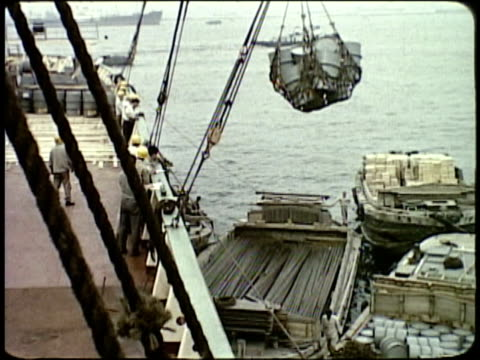 1963 MONTAGE Workers unloading cargo at docks / Japan