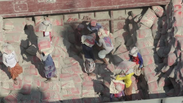 stockvideo's en b-roll-footage met workers unloading cement bags from a ship in gabtoli, on the outskirts of dhaka. the workers earn approximately 3 usd for a ten-hour working day. - zak tas
