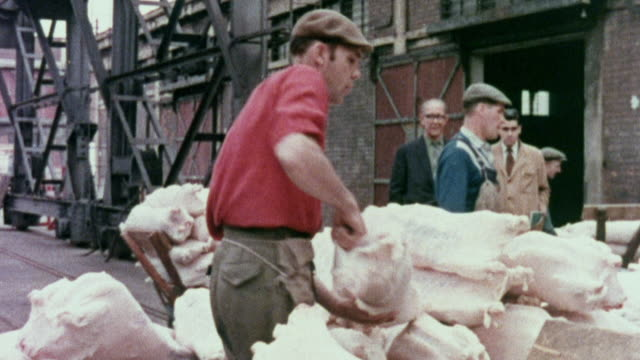 vídeos de stock, filmes e b-roll de 1973 montage workers unloading produce in market / united kingdom - 1973
