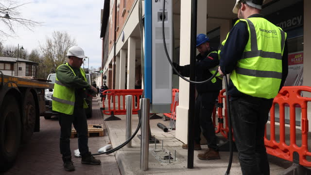 workers use a crane to lower a new swarco ag electric vehicle rapid charger unit into position in canterbury, u.k. on thursday, april 8, 2021. - automobile industry stock videos & royalty-free footage