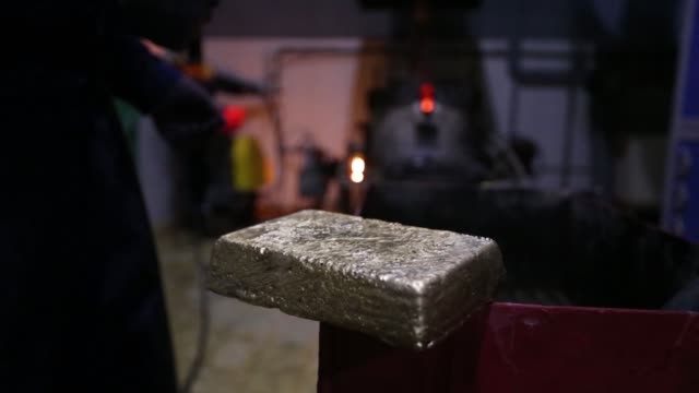 Workers use a hammer and cleaning solution to remove impurities from the surface of a newly cast 175 kilogram gold bar at the Suzdal gold mine...
