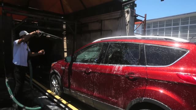 vídeos y material grabado en eventos de stock de workers use brushes to clean a car at ducky's car wash on july 29 2015 in san mateo california as california endures its fourth year of severe... - túnel de lavado de coches