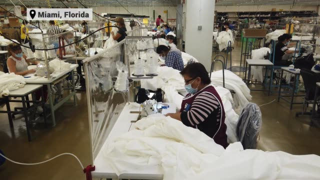 stockvideo's en b-roll-footage met workers use sewing machines to put together isolation gowns and masks at the goodwill south florida facility for doctors working in hospitals on... - geproduceerd segment