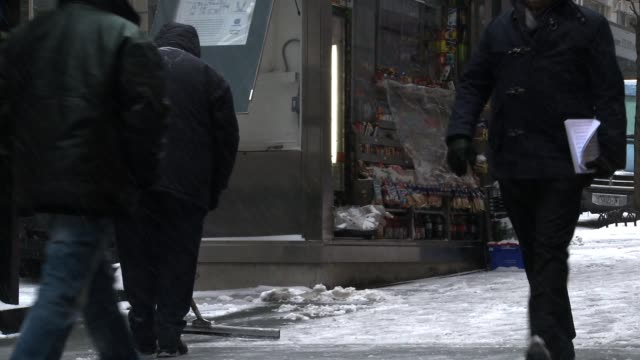 vídeos de stock e filmes b-roll de workers use shovels and squeegees to remove snow on city sidewalks at madison avenue and 42nd st. - pá para neve