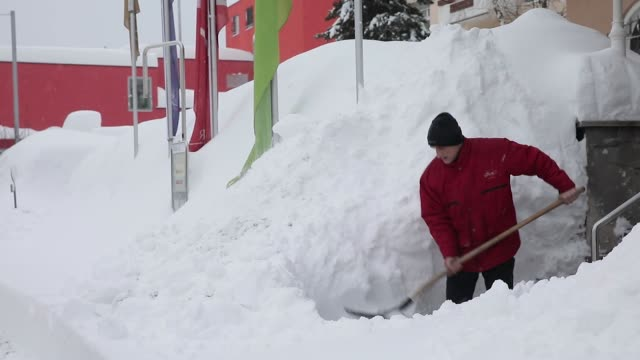vídeos de stock, filmes e b-roll de workers use shovels to clear fresh snow from the path leading to the rixos fluela davos hotel in davos, switzerland, on sunday, jan. 21 a bulldozer... - 2018
