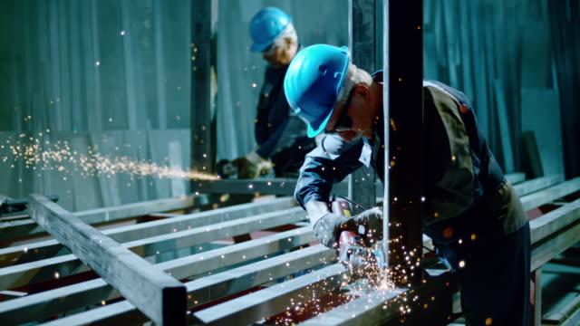 stockvideo's en b-roll-footage met slo mo ld workers using angle grinders creating metal sparks - metaalindustrie