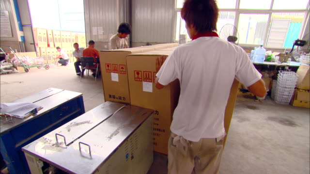 ms workers using dolly to transport three large cartons at aihu electric bicycle factory, tianjin, tianjin, china - chinese culture stock videos & royalty-free footage