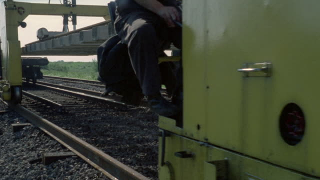 1969 montage workers using equipment to lay reinforced concrete sleepers and rails along the british railways / united kingdom - british rail stock videos & royalty-free footage