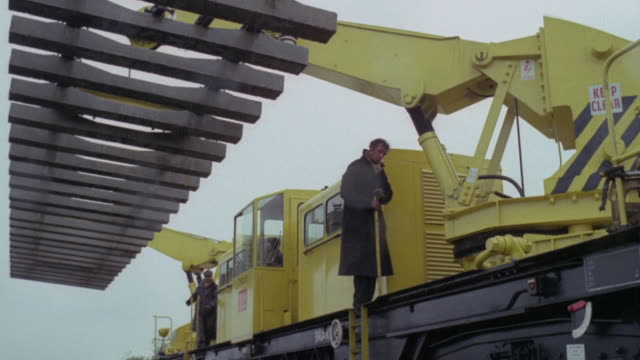 1969 montage workers using machines to lay new rail sections along the british railways / united kingdom - british rail stock videos & royalty-free footage