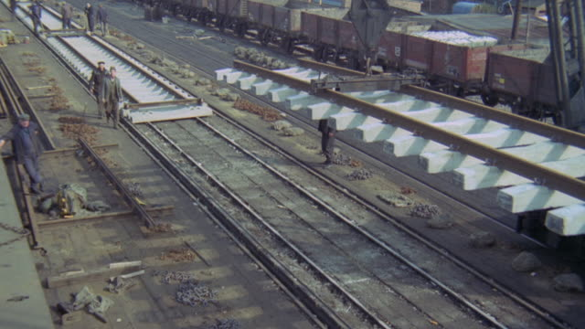 1969 montage workers using machines to lay reinforced concrete sleepers and rails along the british railways / united kingdom - british rail stock videos & royalty-free footage