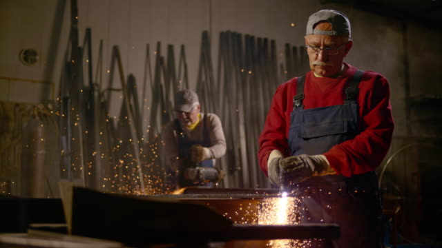 slo mo ds workers using metal cutting tools in workshop - only mature men stock videos & royalty-free footage