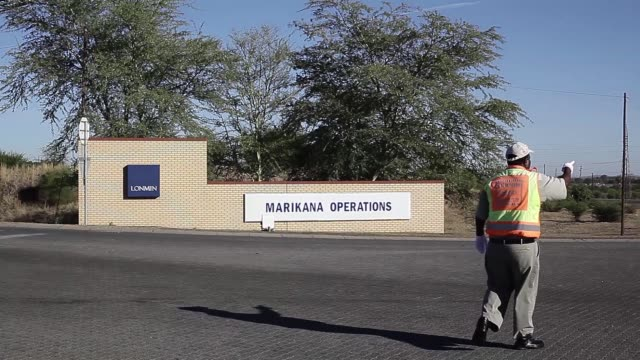 workers walk past the marikana mine operated by lonmin plc as it stands in the distance in marikana south africa on friday nov 6 donkeys graze... - mine shaft stock videos and b-roll footage