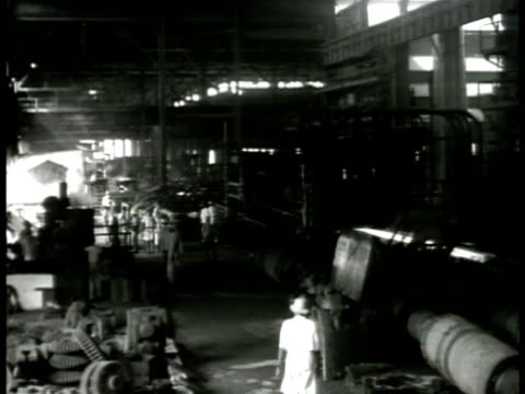 workers walking from factory some w/ shade umbrellas int factory plant hot ingot moving on roller conveyor worker spooning hot molten iron ore metal... - hinduism stock videos & royalty-free footage