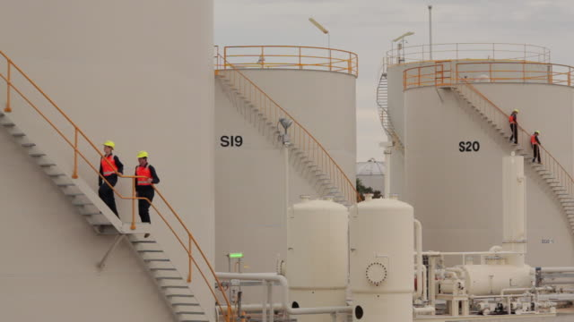 vídeos de stock e filmes b-roll de ws workers walking on sides of storage tanks in refinery / perth, australia - petroquimica