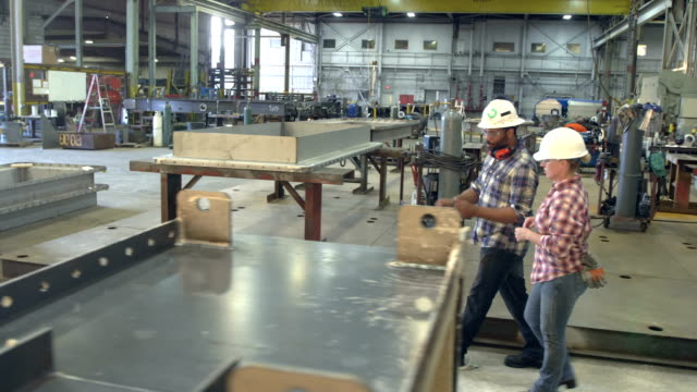 workers walking through metal fabrication shop - dipendente video stock e b–roll