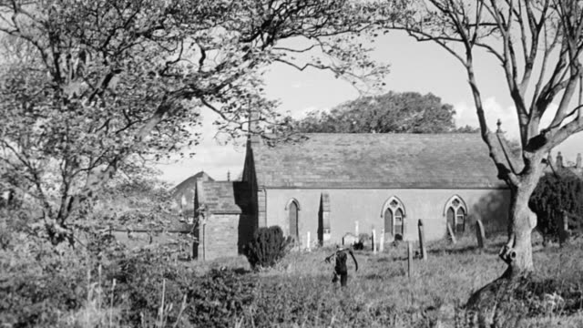 montage workers walking toward mine, laborer carrying scythe outside chapel amongst trees, parish building, pubs, villagers disembarking double decker bus, sea beneath cloudy skies / flimby, england, united kingdom - village stock videos & royalty-free footage