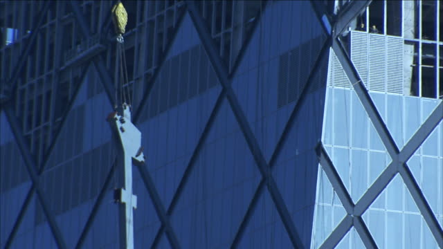 workers watch a crane hoist a metal section toward the top of the cctv building. - hoisting stock videos & royalty-free footage