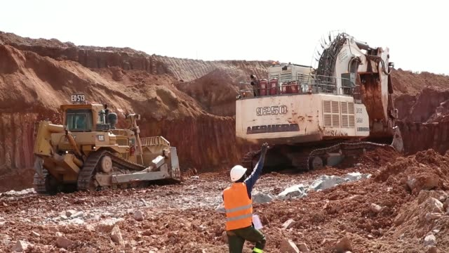Workers watch an excavator in operation on the digging floor of the Gounkoto open pit gold mine part of the LouloGounkoto mine complex operated by...