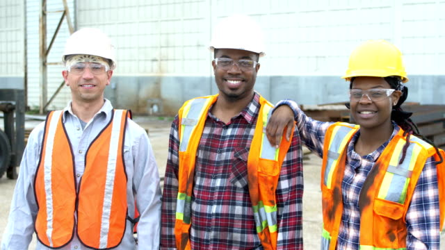 workers wearing hardhats, safety vests and goggles - focus on foreground stock videos & royalty-free footage