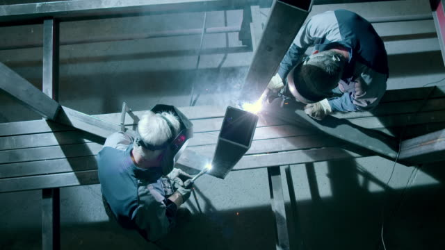 SLO MO CS Workers welding a metal frame in workshop