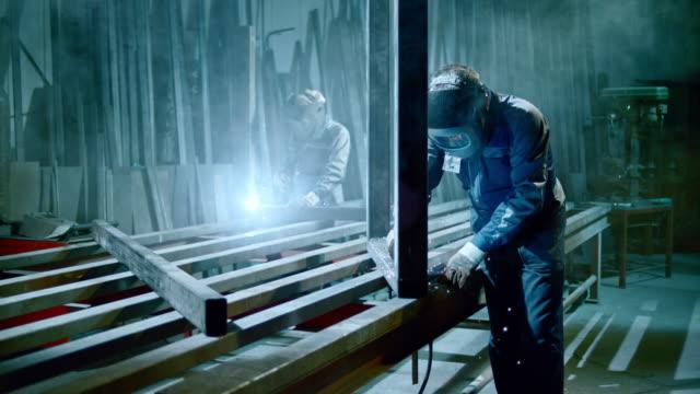 slo mo ld workers welding in the workshop wearing protecting helmet - welding helmet stock videos & royalty-free footage