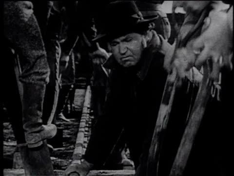 1945 reenactment workers working on railroad construction / united states - フランク キャプラ点の映像素材/bロール