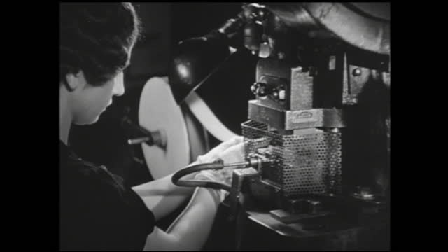 vídeos y material grabado en eventos de stock de workers working on the assembly line manufacturing various parts; wires being inserted into glass tubes and falls into a pile; spinning metal parts;... - 1940 1949