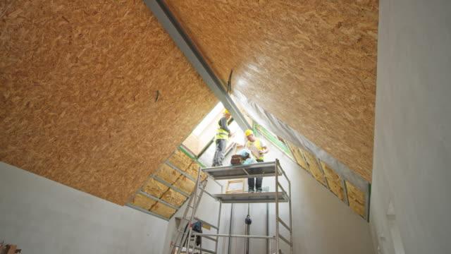 vidéos et rushes de ld travailleurs travaillant sur l'échafaudage sous le plafond - lockdown
