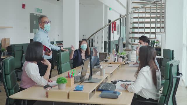 オフィスの朝でお互いにオフィスの挨拶に戻ってフェイスマスクを持つ働くアジアの中国人の先輩 - 1日目点の映像素材/bロール