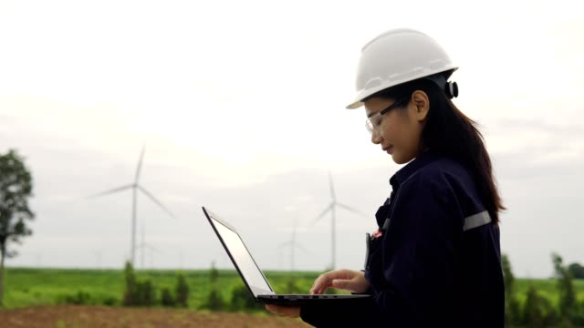 working asian engineers look at a laptop in hands she checking the wind turbine system with a laptop in wind turbines farm. environmental energy concept. - females stock videos & royalty-free footage