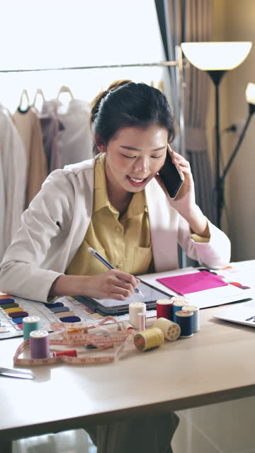 working asian fashion designer talking on phone with her customer for designer solution, vertical - designer clothing stock videos & royalty-free footage