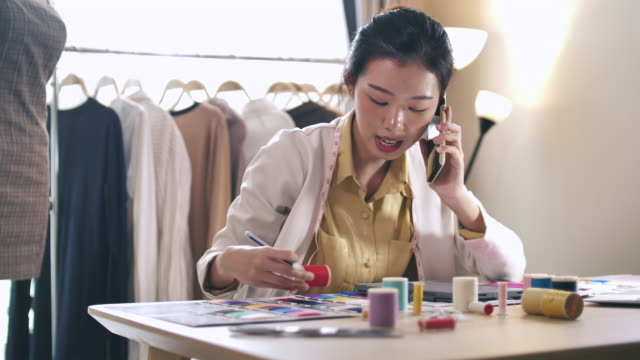 working asian fashion designer talking on phone with her customer for designer solution - tailored clothing stock videos & royalty-free footage