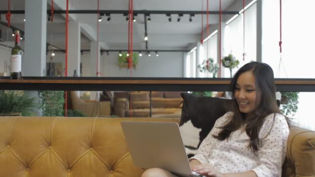 vídeos de stock e filmes b-roll de working at home concept:southeast asia girl working on sofa at home - ecrã tátil