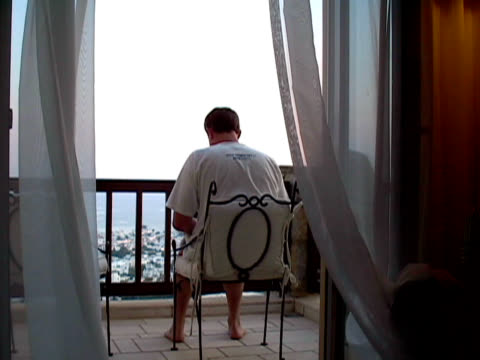 Working Behind Curtains.  Man Uses Laptop on Balcony / Patio