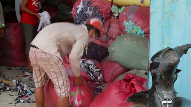 working conditions for young men working at the plastic recycling center at the city dump in phnom penh, cambodia - phnom penh stock videos and b-roll footage