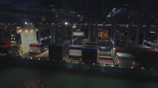 vídeos de stock e filmes b-roll de working crane and container ship in industrial port at night, aerial video - pier