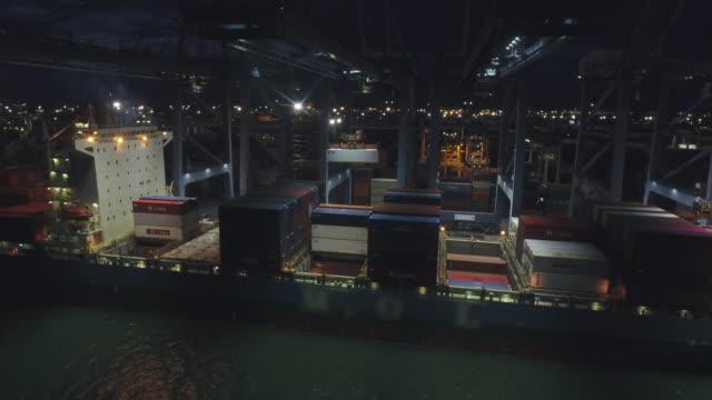 vídeos y material grabado en eventos de stock de grúa de trabajo y buque contenedor en puerto industrial por la noche, vídeo aéreo - embarcadero