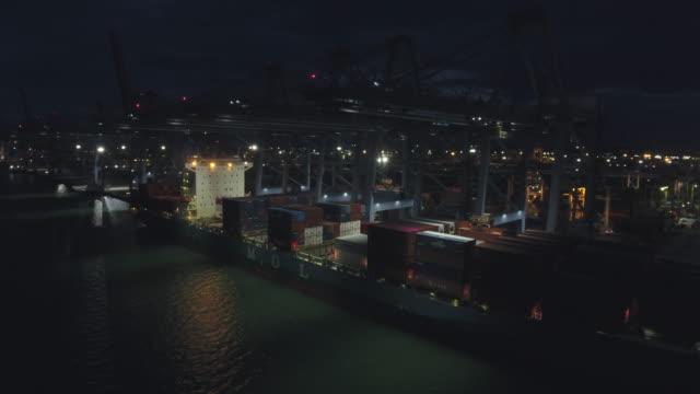 gru funzionante e nave portacontainer nel porto industriale di notte - porto marittimo video stock e b–roll