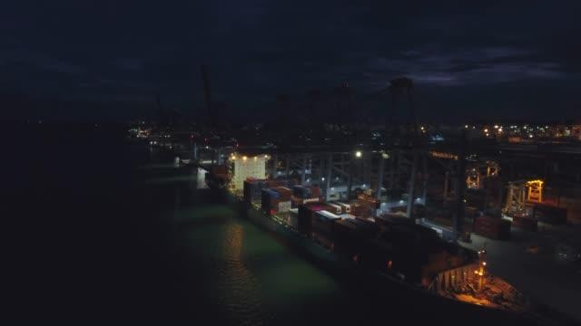 vídeos y material grabado en eventos de stock de grúa de trabajo en el buque contenedor en puerto industrial por la noche, video aéreo - en lo alto posición descriptiva