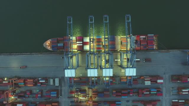 vídeos y material grabado en eventos de stock de grúa de trabajo en buque contenedor en puerto industrial por la noche, vídeo aéreo - grulla de papel